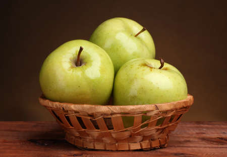 apples basket: juicy green apples in basket on wooden table on brown background