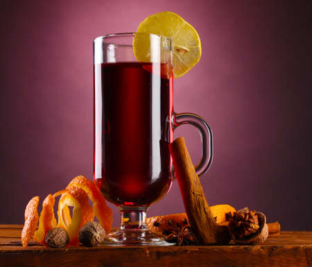 mulled wine in the glass, spice and lemon on purple background photo