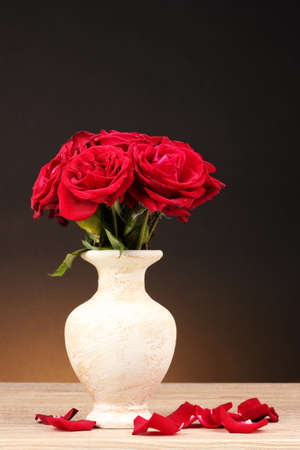 vase: Beautiful red roses in vase on wooden table on brown background