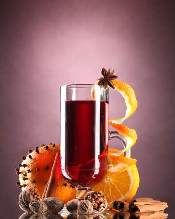 grog: mulled wine in the glass, spice and orange on purple background Stock Photo