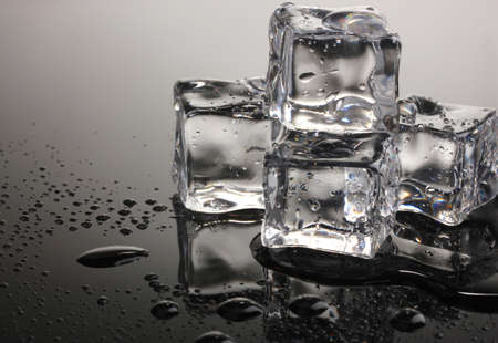 froze: Melting ice cubes on grey background