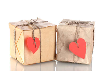 Two small parcels with blank heart-shaped labels isolated on white photo