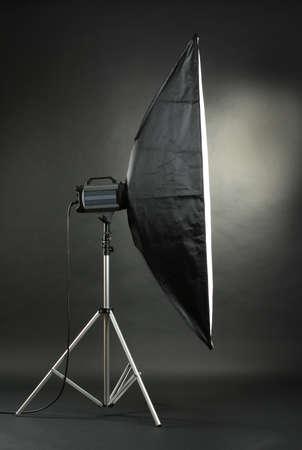 Studio flash with soft-box on black studio background photo