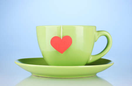 Green cup with saucer and tea bag with red heart-shaped label on blue background photo