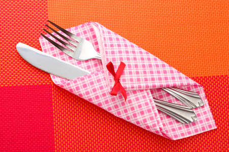 Fork and knife in a plaid cloth with a bow on a red tablecloth photo