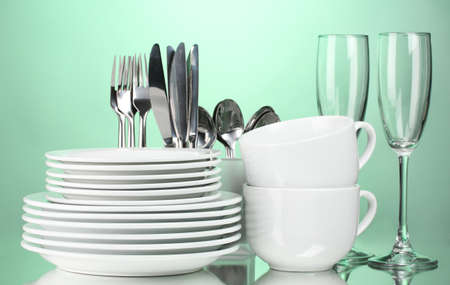 Clean plates, glasses, cups and cutlery on green background photo