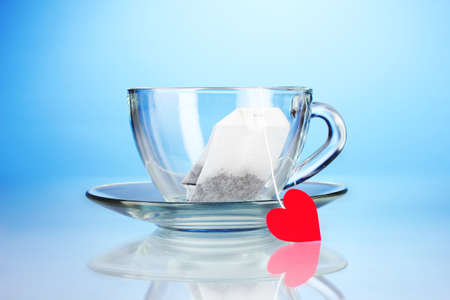 Glassy cup with saucer and tea bag with red heart-shaped label on blue background photo