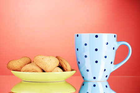 Heart-shaped cookies on plate and cup on red background photo