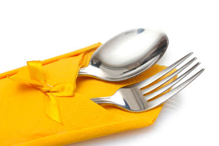 Fork and spoon in a yellow cloth with a bow isolated on white photo