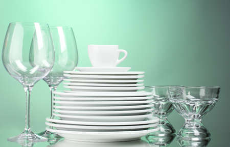 Clean plates, cup and glasses on green background