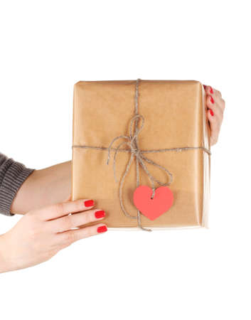 Parcel with blank heart-shaped label in woman's hand isolated on white photo