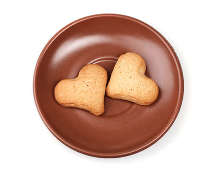 Two heart-shaped cookies on brown saucer isolated on white Stock Photo - 12109581