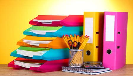bandejas de papel brillante y papel sobre la mesa de madera sobre fondo amarillo Foto de archivo