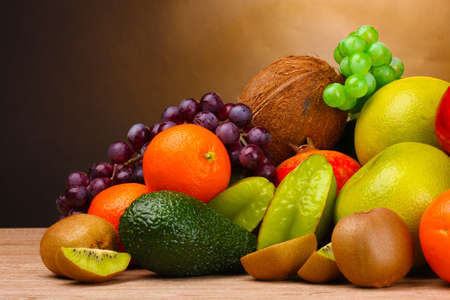 Assortment of exotic fruits on wooden table on brown background photo