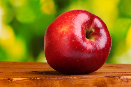 juicy red apple on wooden table on green background photo