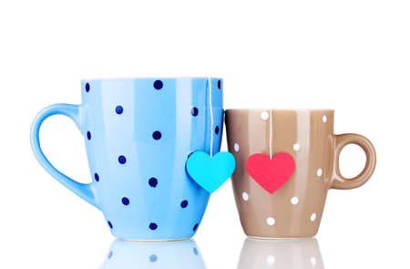 Two cups and tea bags with red and blue heart-shaped label isolated on white photo