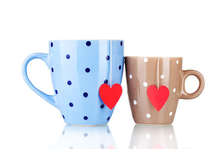 Two cups and tea bags with red heart-shaped label isolated on white photo