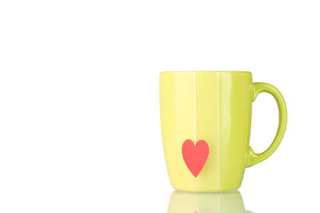 Green cup and tea bag with red heart-shaped label isolated on white photo