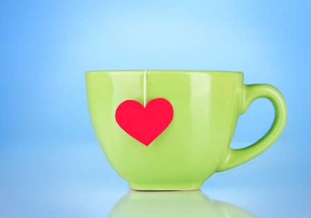Green cup and tea bag with red heart-shaped label on blue background photo