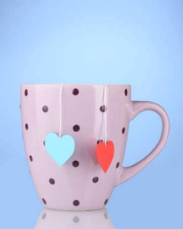 Pink cup and two tea bags with red and blue heart-shaped label on blue background photo