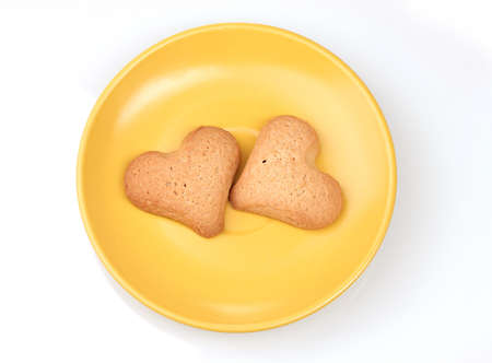 Two heart-shaped cookies on yellow saucer isolated on white Stock Photo - 12143844