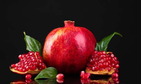 ripe pomegranate fruit with leaves on black background photo