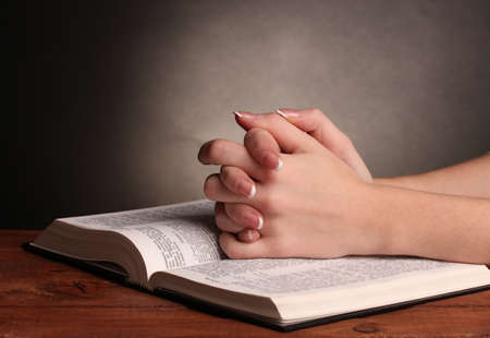 to believe: Hands folded in prayer over open russian Holy Bible on black background