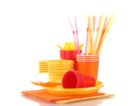 Bright plastic tableware and napkins isolated on white photo