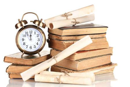 the arts is ancient: Pile of old books with clock and scroll isolated on white