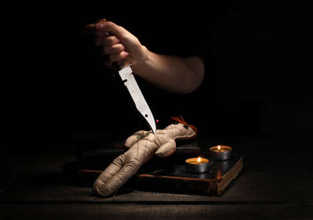 deadman: Voodoo doll girl pierced by knife on a wooden table in the candlelight Stock Photo