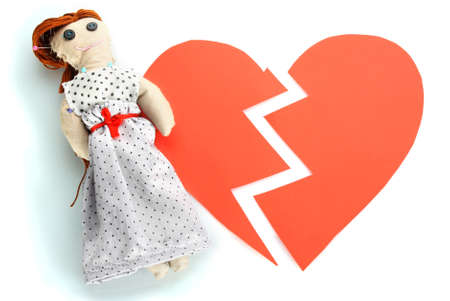 Voodoo doll girl on the broken heart isolated on white photo
