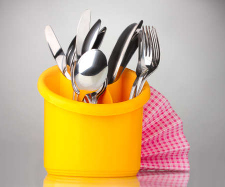 Kitchen cutlery, knives, forks and spoons in yellow stand with pink napkin on grey background photo