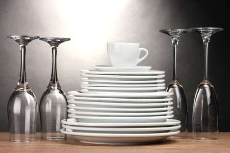 Clean plates, glasses and cup on wooden table on grey background photo
