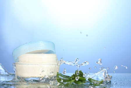 Opened jar of cream in water splash on blue background photo