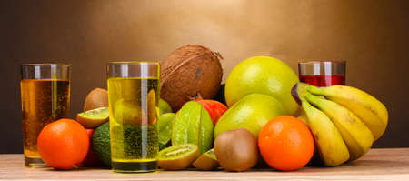 Assortment of exotic fruits and juice on wooden table on brown background photo