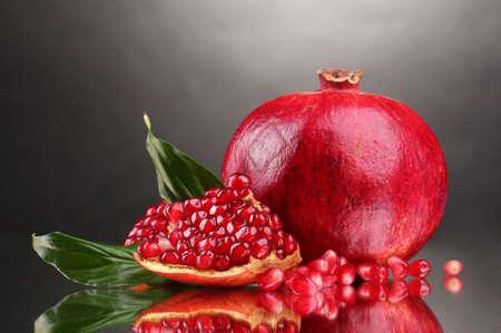 ripe pomegranate fruit on gray background photo