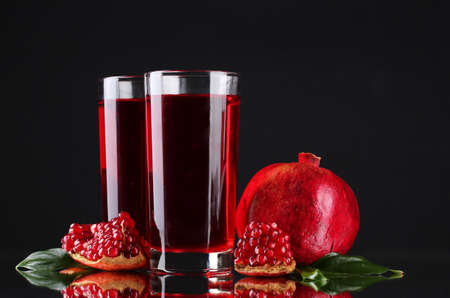pomergranate: ripe pomergranate and glasses of juice on black background