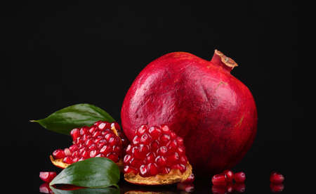 ripe pomegranate fruit with leaves on black background photo