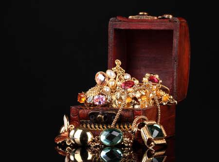 cofre del tesoro: El pecho de madera llena de joyas de oro sobre fondo negro Foto de archivo