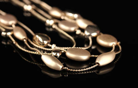 beautiful gold necklace on black background photo