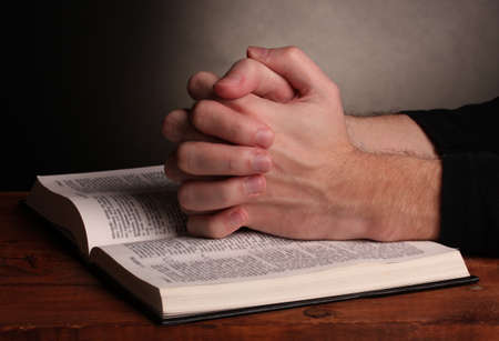 folded hands: Hands folded in prayer over a Holy bible on wooden table on grey background Stock Photo