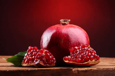 ripe pomegranate fruit with leaves on wooden table on red background Stock Photo - 12144609
