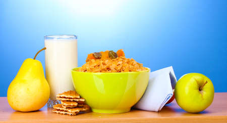 tasty cornflakes in green bowl and glass of milk on wooden table on blue background Stock Photo - 12144582