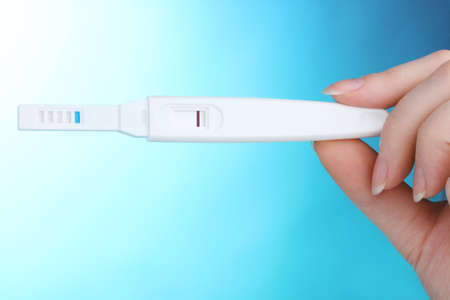 pregnancy test in hand on blue background photo