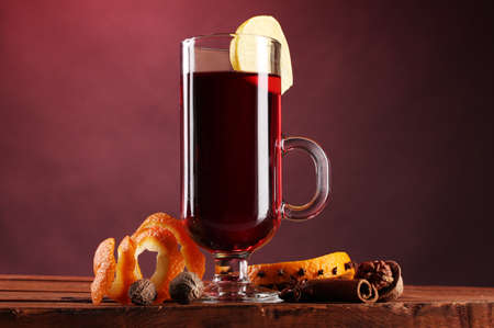 mulled wine in the glass, spice and lemon on red background photo