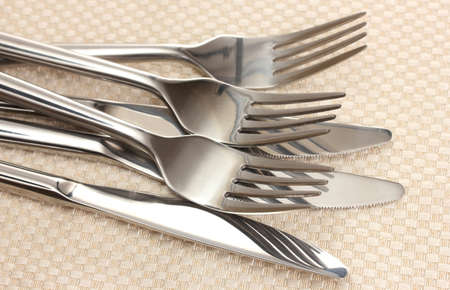 Forks and knives on a beige tablecloth Stock Photo - 12225221