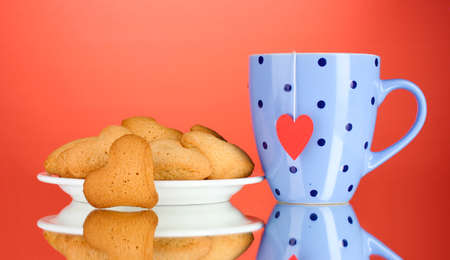 Heart-shaped cookies on plate and cup with tea bag on red background photo