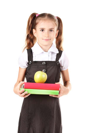 beautiful little girl in school uniform, books and apple isolated on white photo