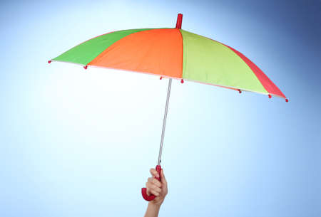 Multi-colored umbrella in hand on blue background photo