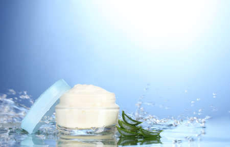 health care protection: Opened jar of cream in water splashes on blue background